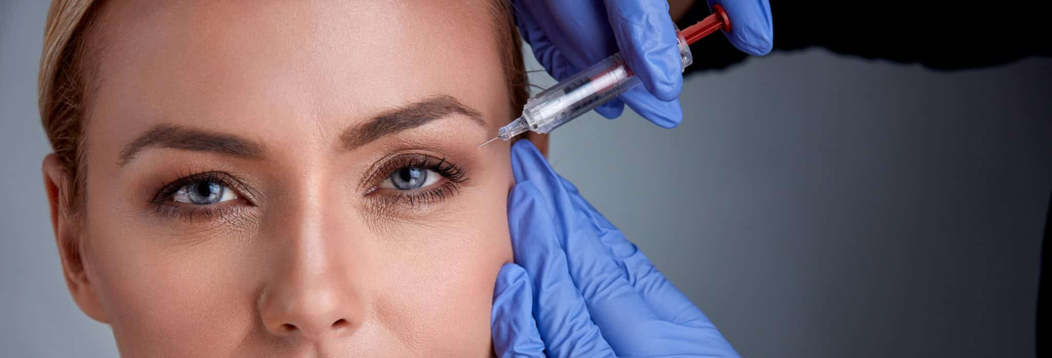 Woman receiving botox procedure by doctor
