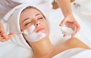 Woman having facial mask spread onto face