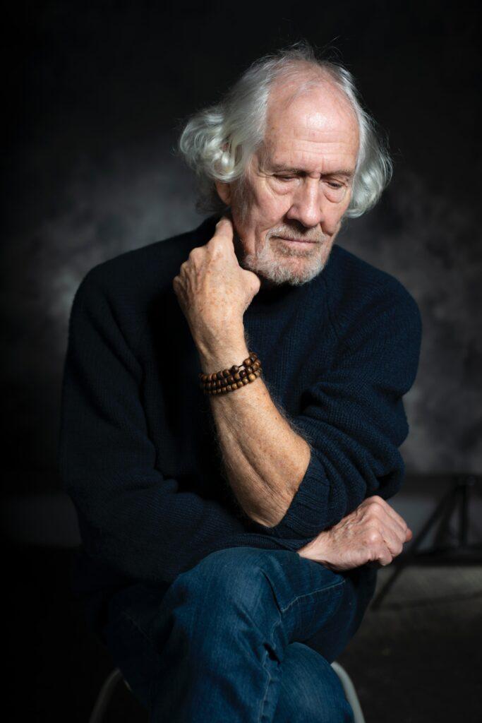 An older man sits